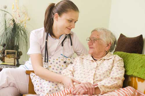 Home healthcare nurse providing comfort to elderly patient