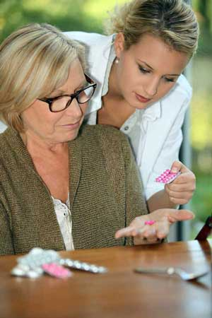 A skilled registered nurse helping a patient with her pills in home setting