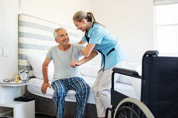 Smiling nurse assistant helping a patient to stand