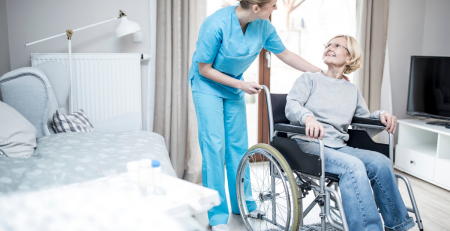 Nurse assisting elderly woman in wheelchair