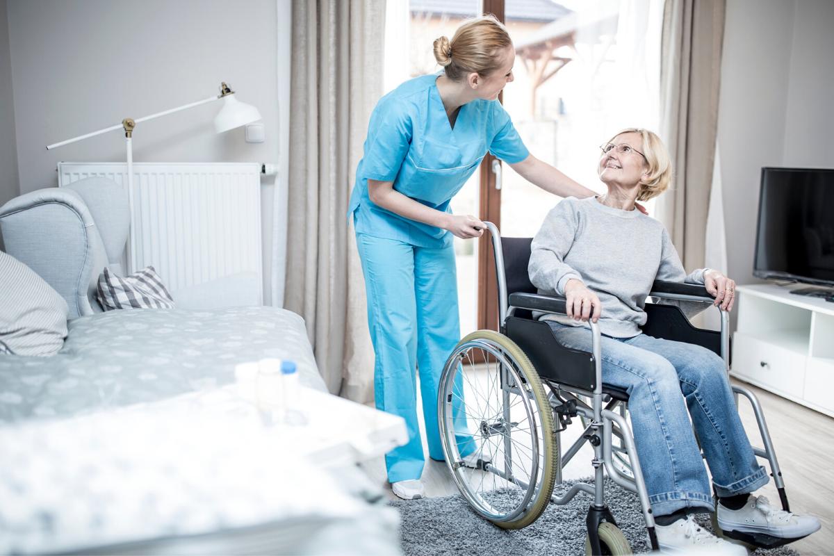 Nurse assisting elderly woman in wheelchair