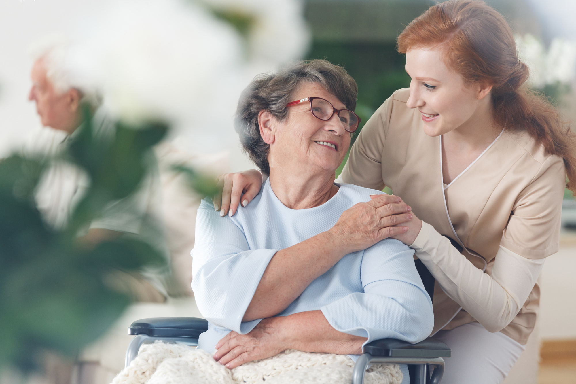 An Older Female Patient in a Wheelchair Being Assisted and Encouraged by a Home Healthcare Aide