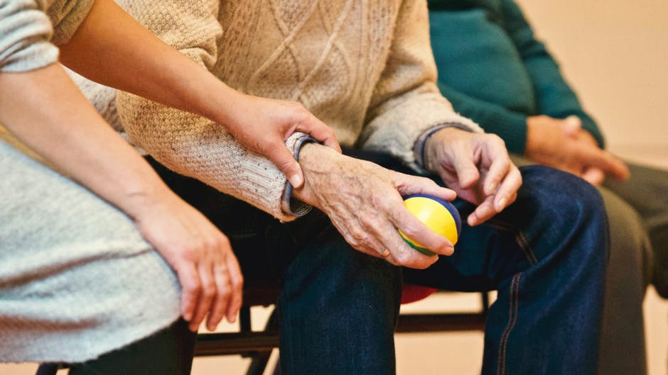 Home Health Care Agency Worker Assisting Patient With Hand Exercise